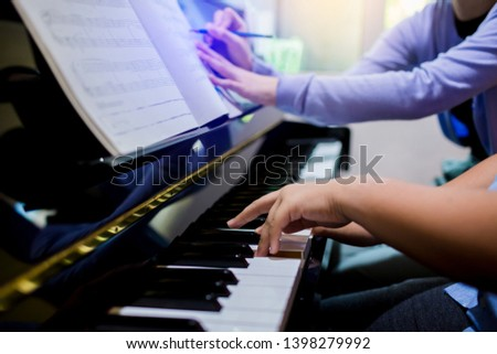 woman teaching a boy to play the piano with writing on music notation, two people playing piano to learning class, There are musical instrument, the concept of learning music, selective focus. #1398279992