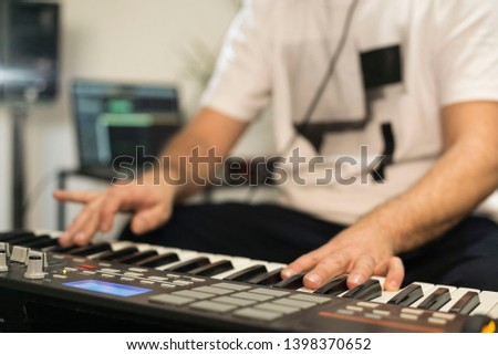 Close up of professional musician recording midi keyboard in digital studio at home. He is surrounded with instruments and midi controller. Music production concept. #1398370652