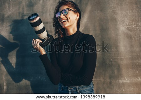 Young woman photographer with her professional camera smiling against oliphant backdrops. Woman photographer with digital camera. Royalty-Free Stock Photo #1398389918