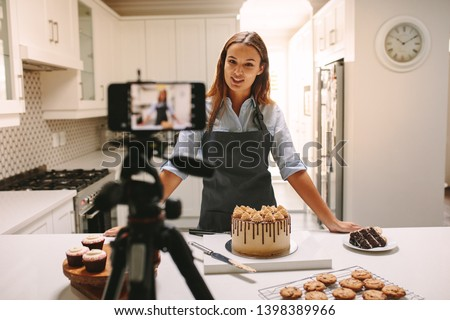 Young woman vlogger baking and recording video for food channel. Female pastry chef vlogging with her mobile phone mounted on a tripod in kitchen. #1398389966