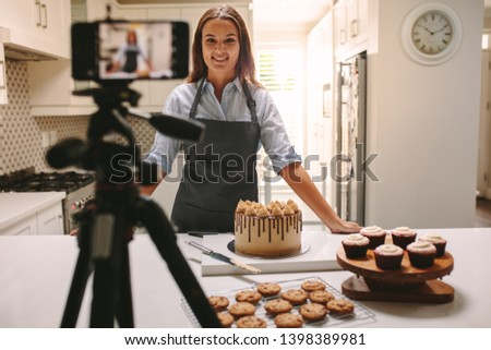 Woman recording video in her home kitchen. Pastry chef creating content for video blog. #1398389981