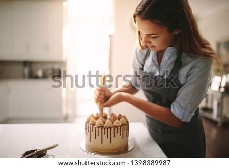 Woman decorating chocolate cake in the kitchen. Female chef making a cake at home. #1398389987