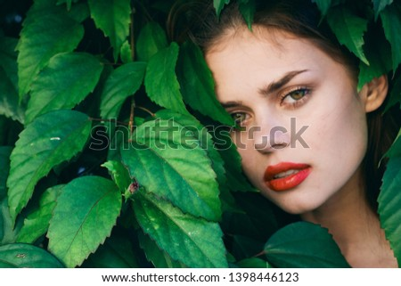 Beautiful woman Exotic Makeup on the face red lips green shrub #1398446123