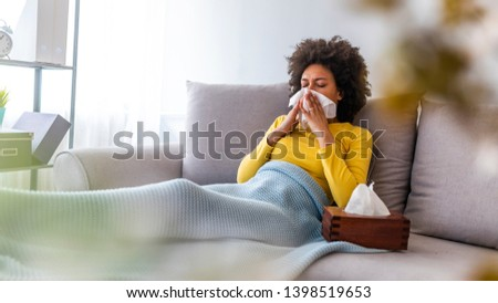 Sick young woman sitting on sofa blowing her nose at home in the sitting room. Photo of sneezing woman in paper tissue. Picture showing woman sneezing on tissue on couch in the living-room Royalty-Free Stock Photo #1398519653