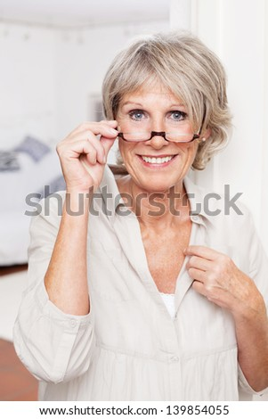 Portrait of an attractive smiling elderly lady with reading glasses #139854055