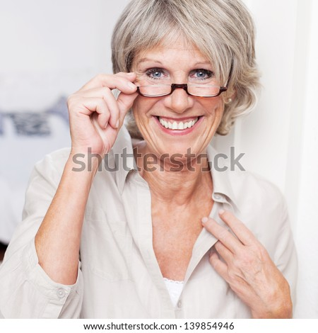 Happy attractive senior lady with a beautiful big smile wearing reading glasses and peering over the top at the viewer #139854946