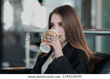 A young beautiful brunette girl in a gray coat is sitting on a bench waiting. Drinking coffee and holding a paper cup with a drink. Gray blurred background. #1398558395
