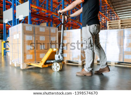 warehouse worker is working with hand pallet truck or pallet jack and shipments in distribution warehouse. #1398574670