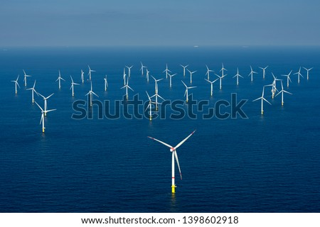 Alternative energy - Aerial view of offshore windmill park at sea. Royalty-Free Stock Photo #1398602918