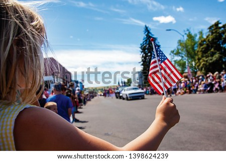 Girl Holding USA Flag at 4th of July Parade Festival Celebration #1398624239