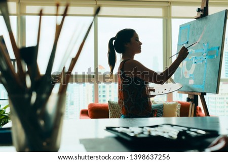 Portrait of young latino woman painting for hobby in her home studio, practicing with paint, brushes, easel and colors. #1398637256