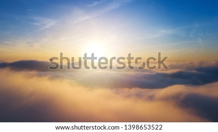 Beautiful sunset cloudy sky from aerial view. Airplane view above clouds #1398653522