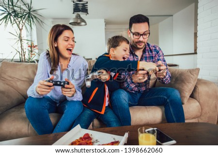 Happy family sitting on a sofa and playing video games and eating pizza #1398662060
