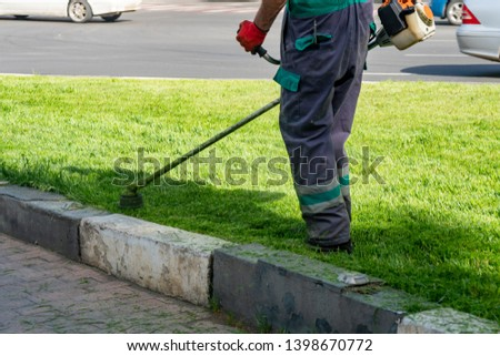The gardener cutting grass by lawn mower, lawn care #1398670772