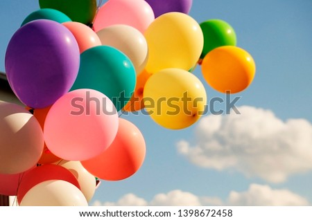 A large bunch of yellow Helium ballons straining on their strings against a sunny sky with white clouds. #1398672458