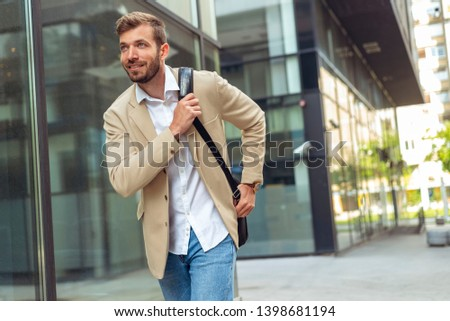 Young businessman looking forward while running along the street #1398681194