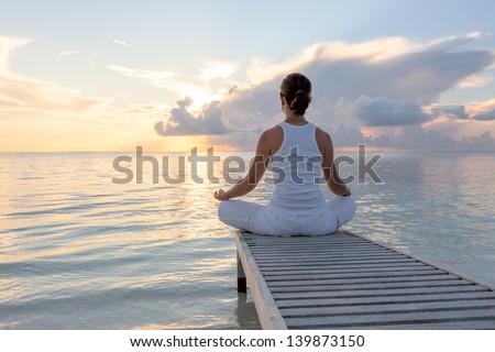 Caucasian woman practicing yoga at seashore Royalty-Free Stock Photo #139873150