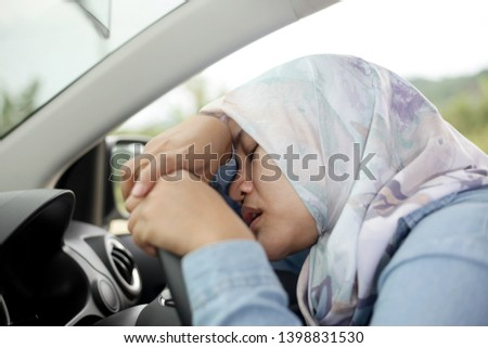 Portrait o Asian muslim lady slept in her car, tired in the trip, taking nap by the side of the road #1398831530