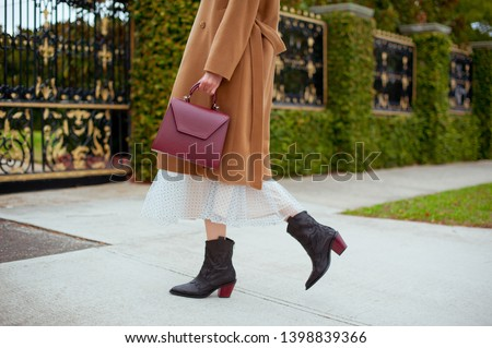 Detail of young fashionable woman wearing beige wool coat, tulle midi skirt and black high heel cowboy boots. She is holding stylish burgundy handbag in hands. Street style. #1398839366