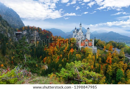 Fall scenery of fairy-tale New Swan Stone Castle (Schloss Neuschwanstein) perched on a rugged hill & surrounded by autumn colors in the beautiful landscape of Bavarian countryside near Fussen, Germany #1398847985