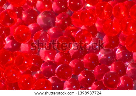 Transparent red hydrogel balls. Red water gel balls with bokeh. Polymer gel Silica gel. Liquid crystal ball with reflection. Red balls texture background #1398937724