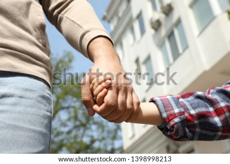 Little child holding hands with his father  outdoors, closeup. Family weekend #1398998213