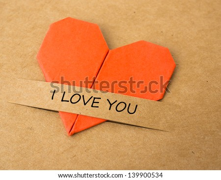"""The heart shape of folded paper on brown screen with """"I love you"""" label"""