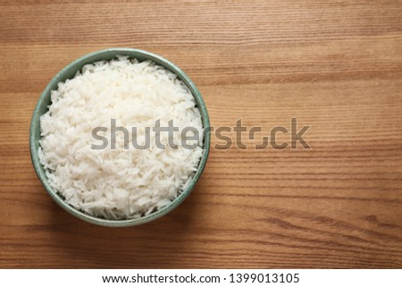 Bowl of tasty cooked rice on wooden background, top view. Space for text #1399013105