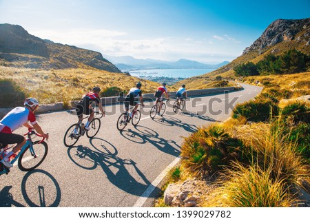 Group of cyclist ride together on road bicycles in beautiful nature. Sunset light, sea in background. #1399029782
