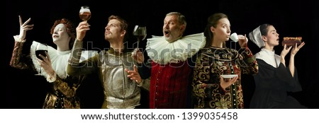 Medieval men and women as a royalty person in vintage clothing drinking wine and coffee and eating on dark background. Concept of comparison of eras, modernity and renaissance. Creative collage. Royalty-Free Stock Photo #1399035458