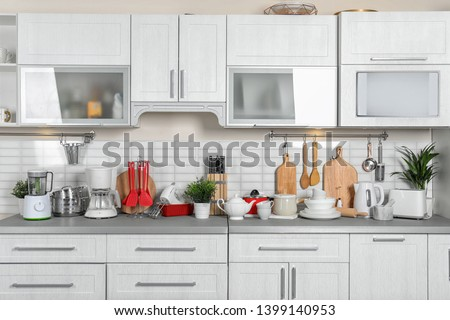 Kitchen interior with clean dishes, cookware and appliances #1399140953