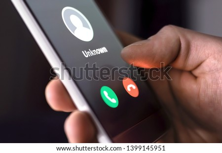 Phone call from unknown number late at night. Scam, fraud or phishing with smartphone concept. Prank caller, scammer or stranger. Man answering to incoming call. Hoax person with fake identity. #1399145951