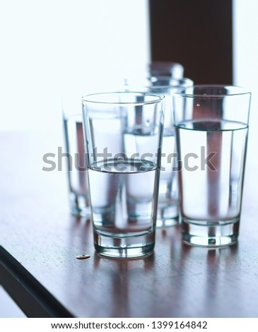 Group of glasses on table filled with still mineral water #1399164842