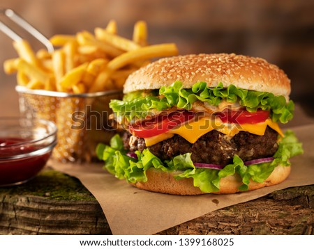 Hamburger and fried potatoes on a wooden table