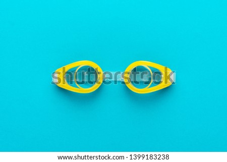 flat lay shot of yellow swimming goggles over turquoise blue background. minimalist photo of swimming goggles with central composition Royalty-Free Stock Photo #1399183238