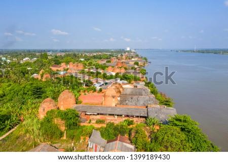 Mang Thit brick kiln in Vinh Long. Burnt clay bricks used in traditional construction of Vietnamese. Mekong Delta, Vinh Long, Vietnam. View from river. #1399189430