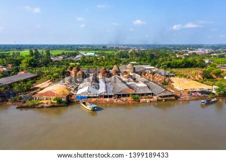 Mang Thit brick kiln in Vinh Long. Burnt clay bricks used in traditional construction of Vietnamese. Mekong Delta, Vinh Long, Vietnam. View from river. #1399189433