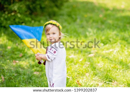 Child carries fluttering blue and yellow flag of Ukraine in field. Ukraine's Independence Day. Flag Day. Constitution day. Girl in traditional embroidery with flag of Ukraine #1399202837