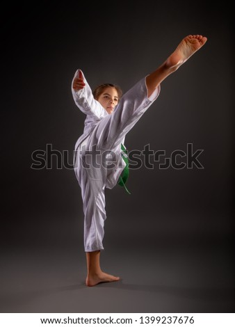 A little girl in a traditional white kimono for karate and a green belt performs training exercises against a dark background. #1399237676