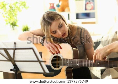Guitar Playing Lesson Music Education Concept. Woman Practice while Sitting on Sofa. Man Hand Touching Strings Showing Chords. Beautiful Blonde Listening Carefully. Inspiration for Musical Performance #1399275749