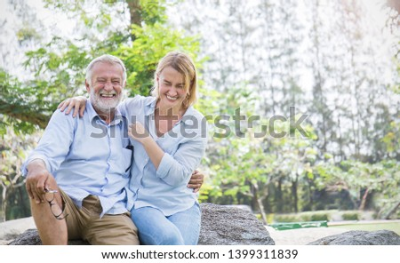 Happy old elderly caucasian couple smiling in park on sunny day, Senior couple relax in spring summer. Healthcare wellbeing lifestyle elderly retirement love couple together valentines day concept  #1399311839