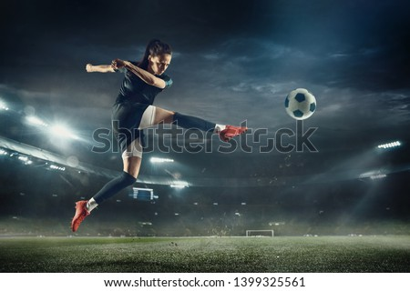 Young female soccer or football player with long hair in sportwear and boots kicking ball for the goal in jump at the stadium. Concept of healthy lifestyle, professional sport, hobby, motion, movement #1399325561