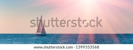 Sailboat in the sea in the evening sunlight over sky background. Luxury summer adventure or active vacation concept. Copy space. Royalty-Free Stock Photo #1399333568