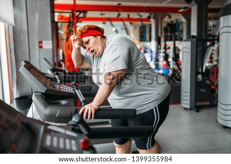 Overweight woman running on a treadmill in gym #1399355984