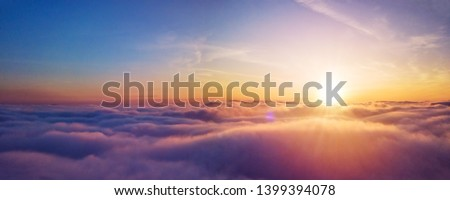 Beautiful sunset cloudy sky from aerial view. Airplane view above clouds Royalty-Free Stock Photo #1399394078