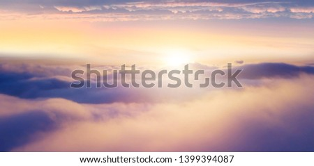 Beautiful sunset cloudy sky from aerial view. Airplane view above clouds #1399394087