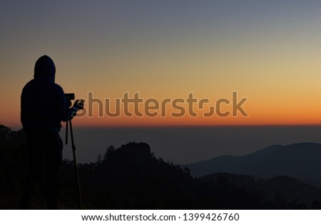silhouette of Travel photographer standing with a camera mounted on a tripod and shooting a time lapse of the sunrise/sunset. man wearing his hood enjoying the mountain view /valley view. #1399426760