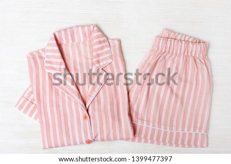 Pink pajamas on white wooden surface. Night suit for sleeping. Copy space. Top view. Flat lay. #1399477397