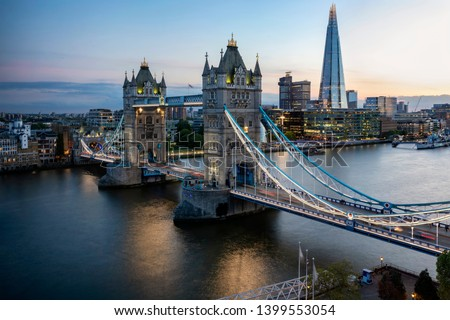 Aerial view to the iconic Tower Bridge, a major tourist attraction in London, UK, during evening time #1399553054