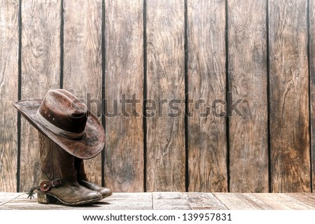 American West rodeo brown felt cowboy hat atop worn and dirty traditional leather boots on a wood deck in front of a vintage ranch barn weathered plank wall